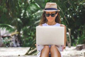 Frau mit Laptop arbeitet am Strand